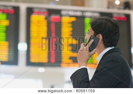 Asian Businessman looking at airport flight timetable and on the phone.