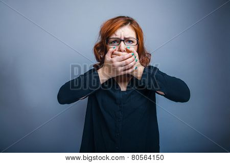 European appearance redheaded girl in glasses covering her mouth