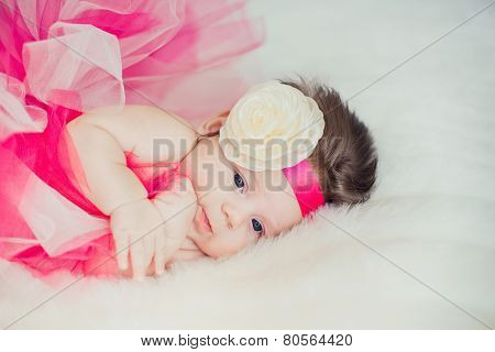 The little girl in the skirt ballerina, crawling on the bed.