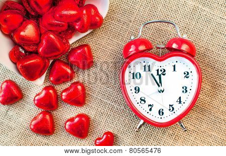 Time For Love. Red Heart Shaped Clock With Sweet Chocolates.