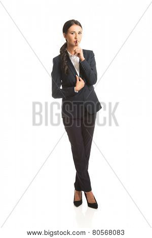 Full length businesswoman making silent sign.