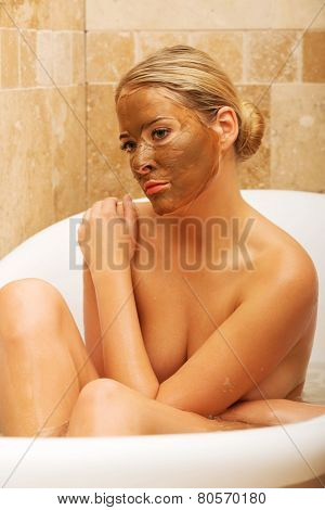 Thoughtful woman sitting in a bath with chocolate mask on face.