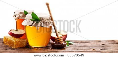 Glass can full of honey, apples and honeycombs on old wooden table. Clipping paths.