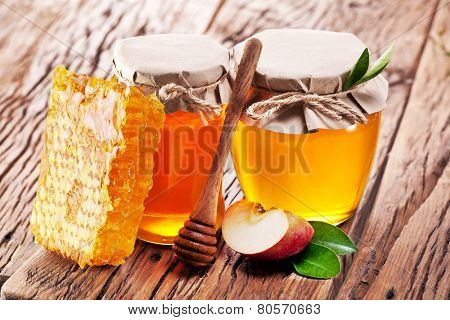 Glass cans full of honey and apple piece and combs on old wooden table.