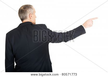 Mature businessman pointing to the right side.