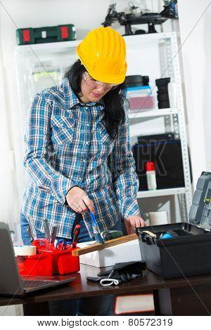 Female carpenter with helmet working in the workshop