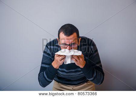 European-looking man years is sick, cold, handkerchief