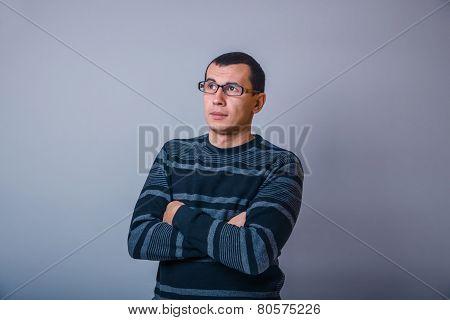 European-looking man of 30 years teacher thinks glasses on gray