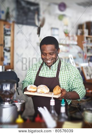 Handsome man in uniform holding fresh pastry in bakery shop