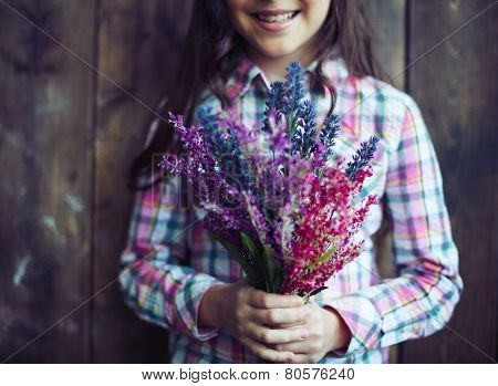 Little girl holding bunch of wildflowers
