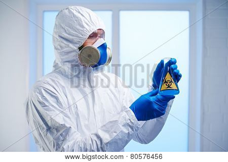 Scientist in protective overall, respirator and gloves holding flask with biohazard fluid in lab