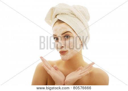 Portrait of a woman with cream lotion on face spreading hands.