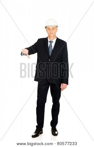Mature engineer businessman showing thumbs down.