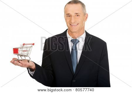 Portrait of businessman holding small shopping cart.