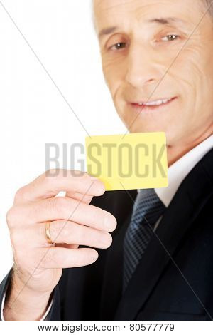 Businessman showing a yellow identity name card.