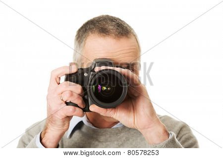Mature man with professional photo camera.