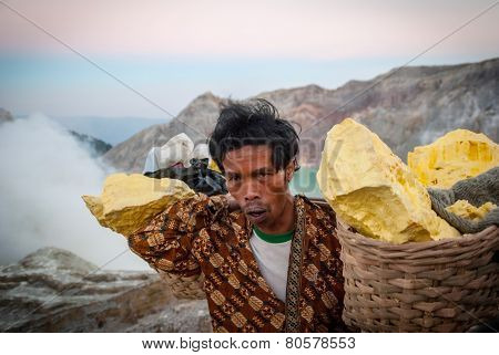 Miner Carying Baskets Of Sulphur At Kawah Ijen Crater, Indonesia