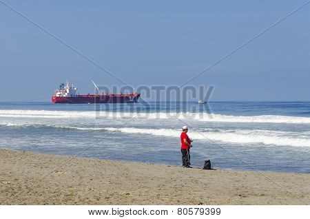 MOLLENDO, PERU, MAY 20, 2014: Chemical tanker named IVER EXAMPLE,  built in 2007, sailing under the flag of Gibraltar, docks at Mollendo waterfront, while a fisherman  fishes in sea