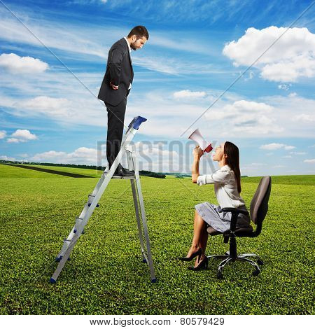 emotional woman with megaphone sitting on chair and screaming at discontented businessman on stepladder. photo at outdoor