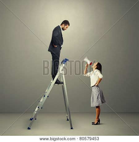 serious man standing on stepladder and looking screaming woman with megaphone. photo in grey empty room