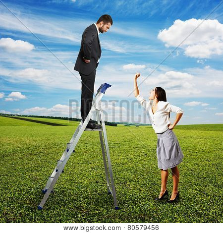dissatisfied woman screaming and showing her fist at serious man on the stepladder. photo at outdoor