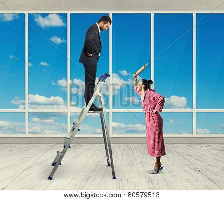 dissatisfied man standing on stepladder and looking down at screaming woman with rolling pin. photo in room with big windows