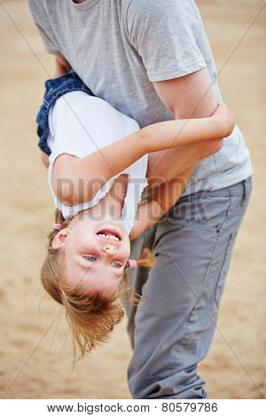 Happy father romping with laughing daughter on beach in summer