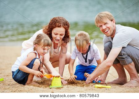 Happy family with two children playing in sand of beach in summer