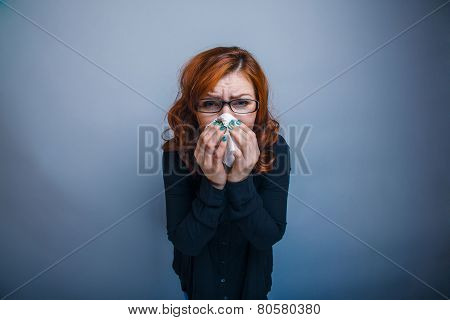 European-looking woman of 30 years is sick, sneezing, handkerchi