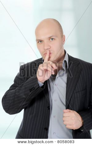 Businessman Holding A Finger To His Mouth.