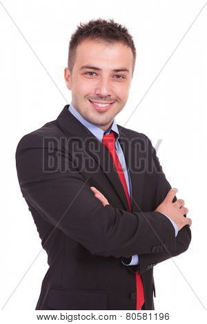 Side view of a happy business man smiling at the camera while holding his hands crossed.
