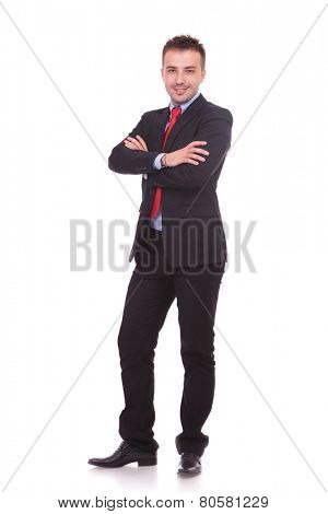 Side view picture of a young business man standing on white studio background with his hands crossed.