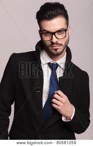 Close up picture of a handsome business man looking at the camera while fixing his blue tie.