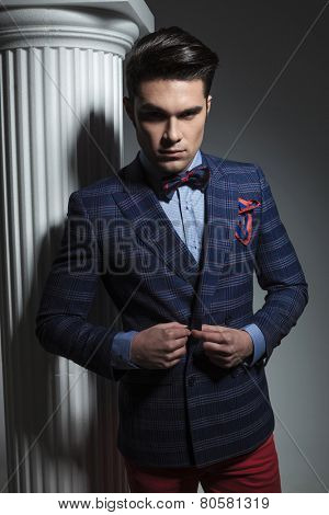 Smart casual fashion man looking down while closing his jacket, near a white column on studio background.