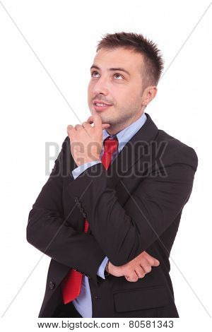 Handsome young business man looking up while holding his hand to his chin thinking.