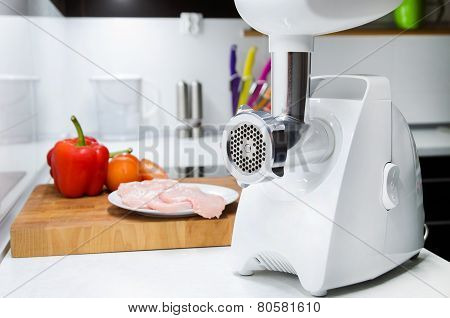Meat Grinder In Modern Kitchen. Vegetables In Background