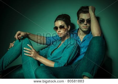 Attractive young fashion man sitting an leaning on a wall while his girlfriend is leaning on him, both looking at the camera.