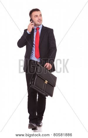 Young business man walking while holding a briefcase and talking on the phone, isolated.