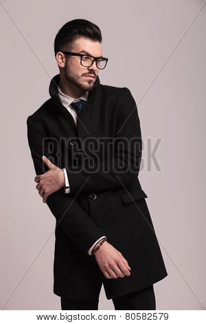 Elegant business man holding his right arm with his left hand while looking away from the camera.