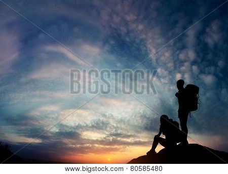 Silhouettes of the hikers relaxing on top of the rock and enjoying sunset