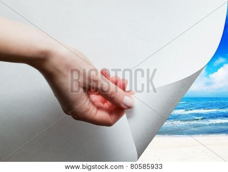 Hand pulling a bottom paper corner to uncover, reveal sunny beach. Page curl, conceptual.