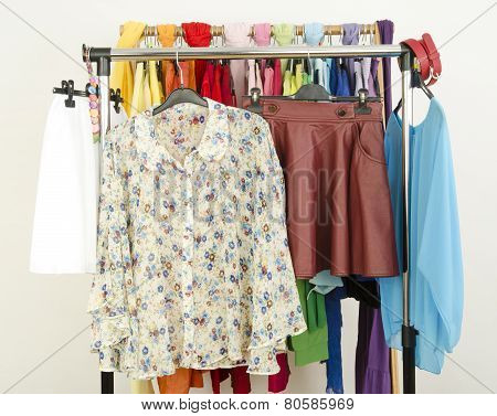 Cute Floral Outfits Displayed On A Rack. Wardrobe With Colorful Summer Clothes And Accessories.