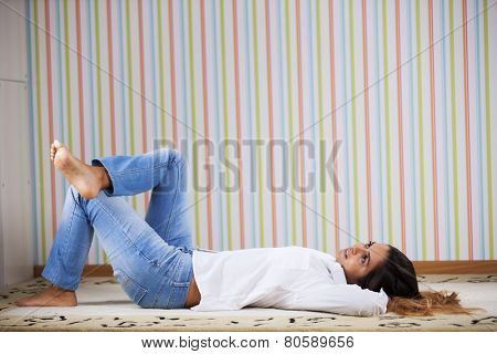 Woman lying in the carpet at home