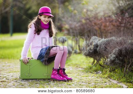 Child ready for travel sit on her briefcase