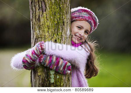 Female child hugging a tree