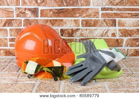 Orange construction helmet and gloves on brick