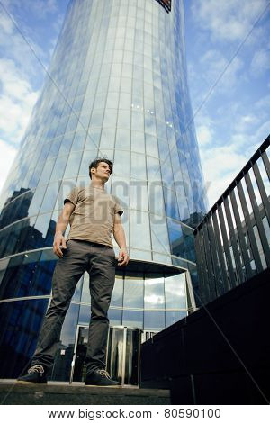 real young man stand in front of modern business building