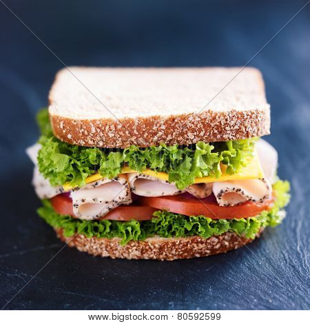 deli meat turkey sandwich on slate surface