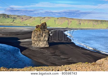 Cape Dirholaey in southern Iceland. On the beach with black volcanic sand is a huge rock in the shape of palms