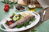 foto of greek  - Mediterranean style organic roasted whole sea bass garnished with Greek salad - JPG